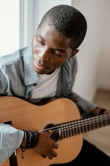 Männlicher musiker, der gitarre auf bett spielt