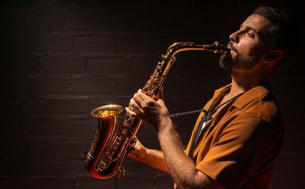 Männlicher musiker, der leidenschaftlich saxophon spielt