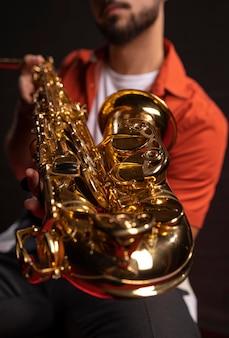 Männlicher musiker, der saxophon hält