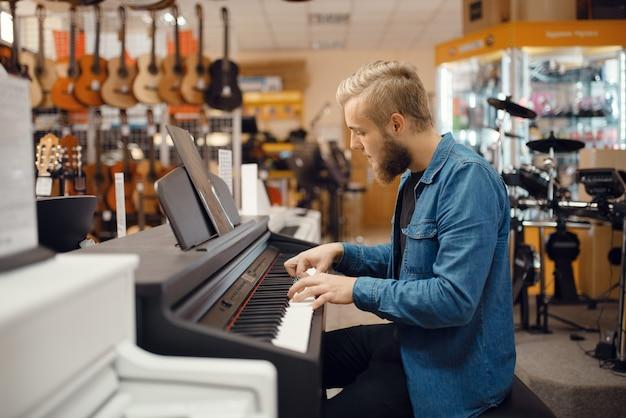 Männlicher musiker, der versucht, auf klavier im musikgeschäft zu spielen. sortiment im musikinstrumentengeschäft, keyboarder, der ausrüstung kauft, pianist auf dem markt