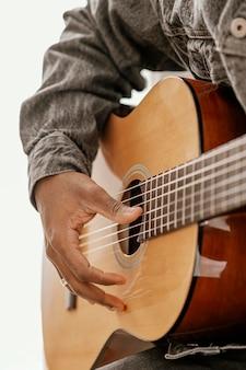 Männlicher musiker, der zu hause gitarre spielt