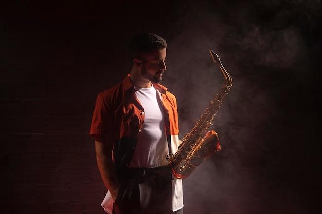 Männlicher musiker im scheinwerferlicht, der ein saxophon hält
