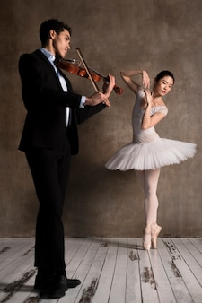 Männlicher musiker mit geige und ballerina im tutu-kleid Kostenlose Fotos