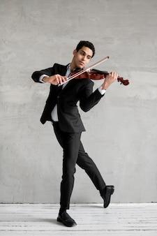 Männlicher musiker tanzt und spielt geige
