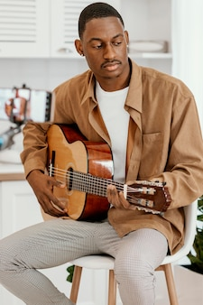 Männlicher musiker zu hause auf stuhl, der gitarre spielt und mit smartphone aufzeichnet