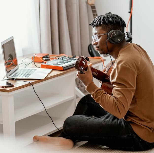 Männlicher musiker zu hause, der gitarre spielt und mit laptop mischt