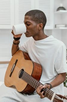 Männlicher musiker zu hause, der gitarre spielt und vom becher trinkt