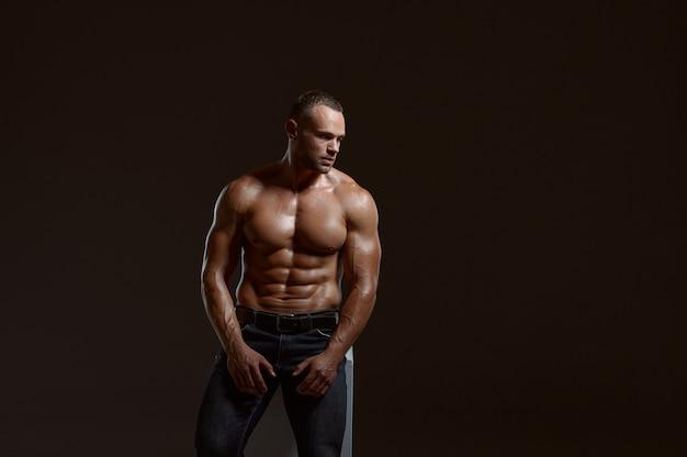 Männlicher muskulöser athlet, der auf würfel im studio sitzt