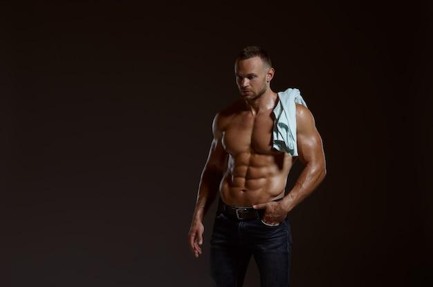 Männlicher muskulöser athlet mit hemd auf seiner schulter