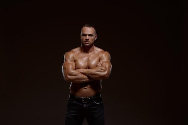 Männlicher muskulöser athlet zeigt seine kraft im studio