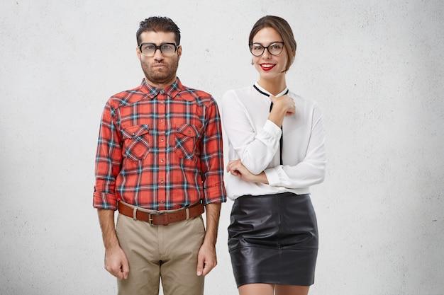 Männlicher nerd steht in formeller kleidung neben seinem schönen gruppenmitglied