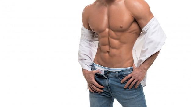Männlicher oberkörper mit perfekter bauchmuskulatur. mann in den blauen jeans und im weißen hemd lokalisiert auf weiß.