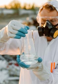 Männlicher ökologe im strahlenanzug, gasmaske. halten sie das reagenzglas mit flüssigkeit, während sie die müllkippe studieren.