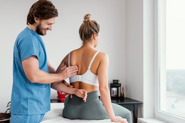 Männlicher osteopathischer therapeut, der das schulterblatt des weiblichen patienten überprüft