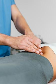 Männlicher osteopathischer therapeut, der den bauch der frau überprüft