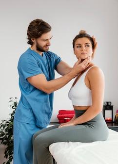 Männlicher osteopathischer therapeut, der die nackenmuskulatur des weiblichen patienten überprüft