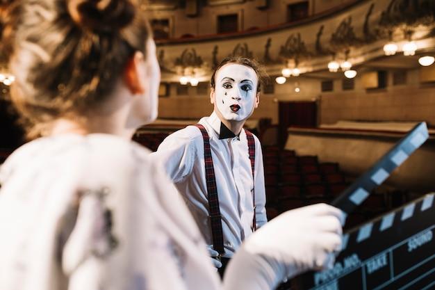 Männlicher pantomime, der am weiblichen pantomimen schmollt, der clapperboard hält