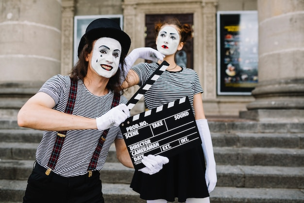 Männlicher pantomime, der clapperboard vor durchdachtem weiblichem pantomimen hält