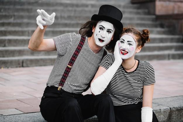 Männlicher pantomime, der dem glücklichen weiblichen pantomimen etwas zeigt