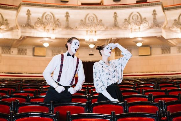 Männlicher pantomime, der den weiblichen pantomimen schaut im zuschauerraum betrachtet