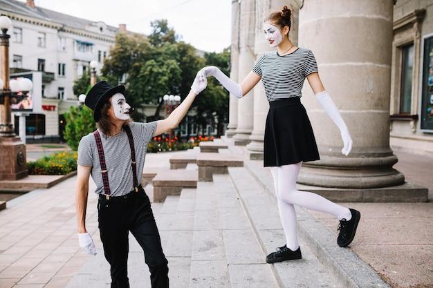 Männlicher pantomime, der den weiblichen pantomimen unterstützt, der hinunter treppenhaus klettert
