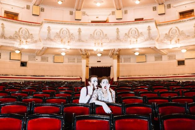 Männlicher pantomime, der in das entsetzte ohr des weiblichen pantomimen flüstert, das auf stuhl im auditorium sitzt