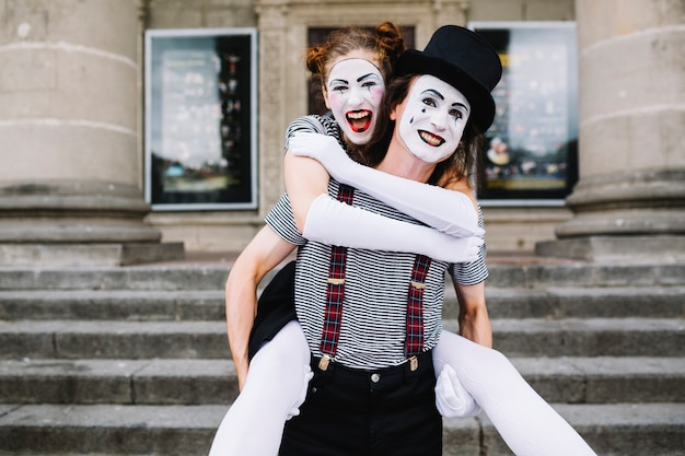 Männlicher pantomime, der piggyback fahrt zum weiblichen pantomimen gibt