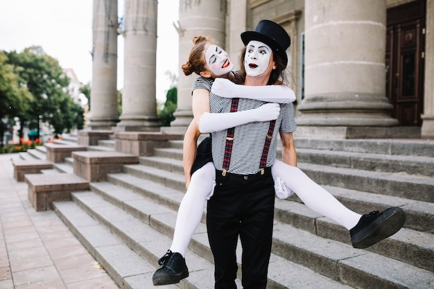Männlicher pantomime, der weiblichen pantomimen auf seinem zurück trägt