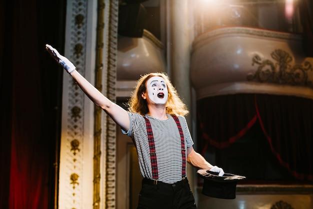 Männlicher pantomimekünstler, der am stadium mit zylinder im auditorium durchführt