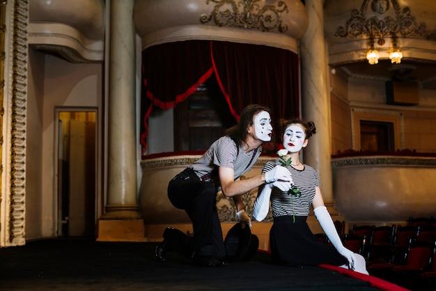 Männlicher pantomimekünstler, der dem weiblichen pantomimen, der auf stadium sitzt, weißrose stieg