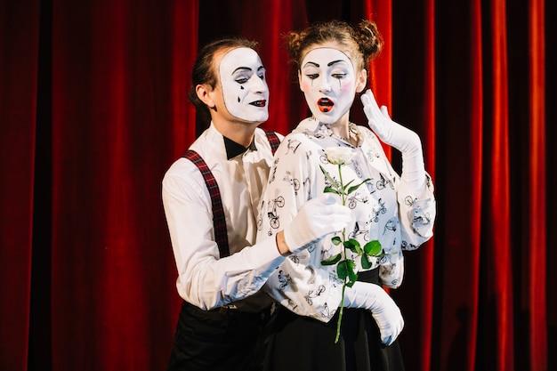 Männlicher pantomimekünstler, der dem weiblichen pantomimen weiße rose gibt