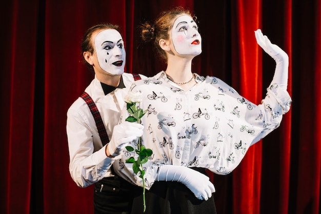 Männlicher pantomimekünstler, der dem weiblichen pantomimenträumen weißrose gibt