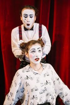 Männlicher pantomimekünstler, der haarbrötchen des weiblichen pantomimen hält