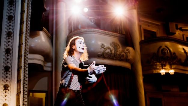 Männlicher pantomimekünstler, der im auditorium probt