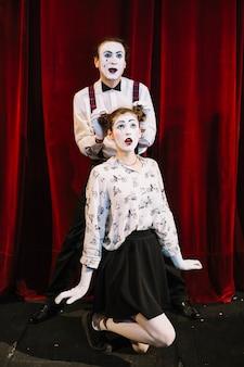 Männlicher pantomimekünstler, der seine hand auf haarbrötchen des weiblichen pantomimen platziert