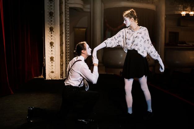 Männlicher pantomimekünstler, der zur hand des weiblichen pantomimen auf stadium küsst