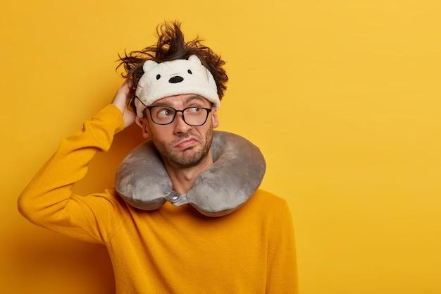 Männlicher passagier, der aufgeblasenes reisekissen über hals und niedliche augenmaske trägt