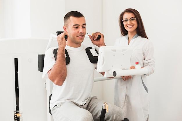 Männlicher patient, der an medizinischer maschine arbeitet