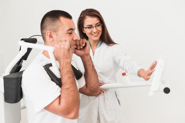Männlicher patient, der auf medizinischer maschine ausarbeitet