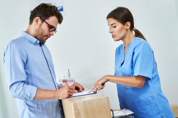 Männlicher patient, der dokumente in der zahnklinik unterschreibt
