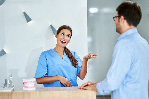 Männlicher patient, der für den zahnarztbesuch in der klinik bezahlt