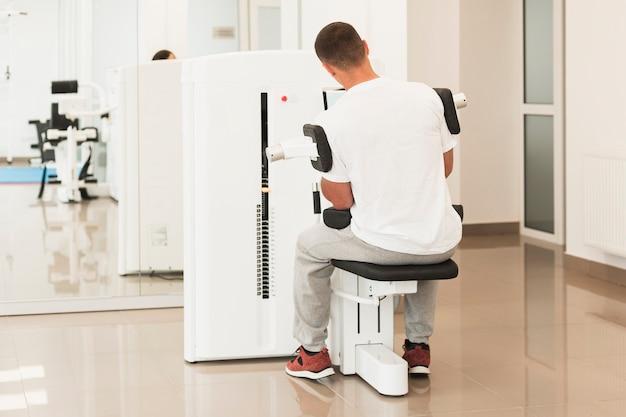 Männlicher patient der hinteren ansicht, der medizinische übungen tut