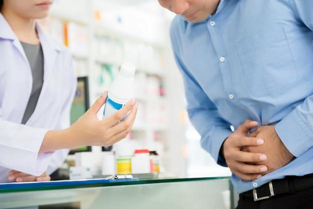 Männlicher patient, der magenschmerzen hat und mit apotheker in der drogerie sich berät