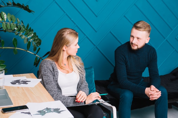 Männlicher patient, der mit dem weiblichen psychologen sitzt mit klemmbrett und stift spricht