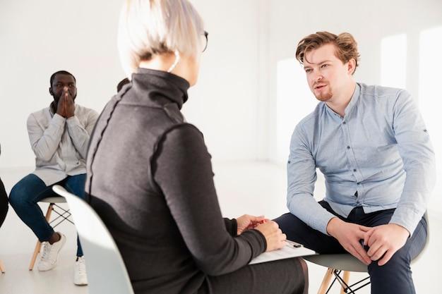 Männlicher patient, der mit rehabilitationsdoktor spricht