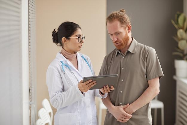 Männlicher patient, der traurig aussieht, weiß von der diagnose von seinem arzt, der etwas auf digitalem tablett zeigt