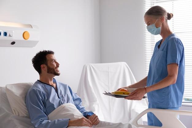 Männlicher patient im bett, der mit einer krankenschwester spricht