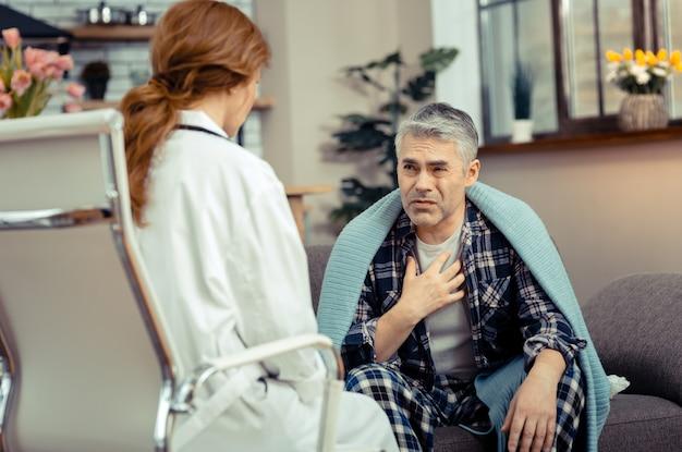 Männlicher patient. unglücklicher trostloser mann, der mit seinem therapeuten spricht, während er gesundheitliche probleme hat