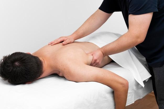 Männlicher patient wird vom physiotherapeuten massiert