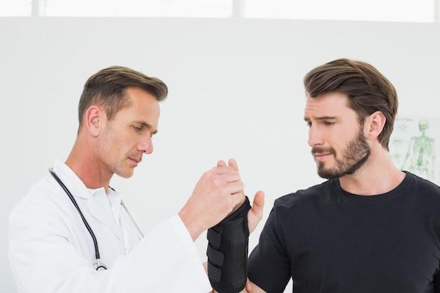 Männlicher physiotherapeut, der a überprüft, bemannt handgelenk